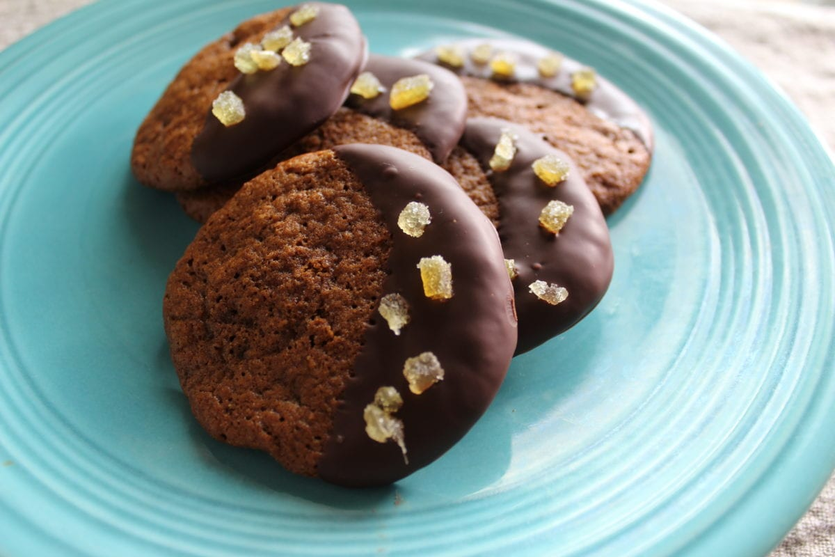 Chocolate dipped molasses cookies on a blue plate