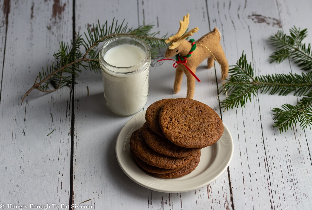 Reindeer ornament next to a glass of milk and plate of cookies