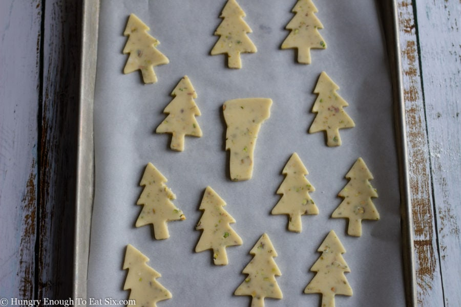 Tree shaped cookies on a lined baking sheet