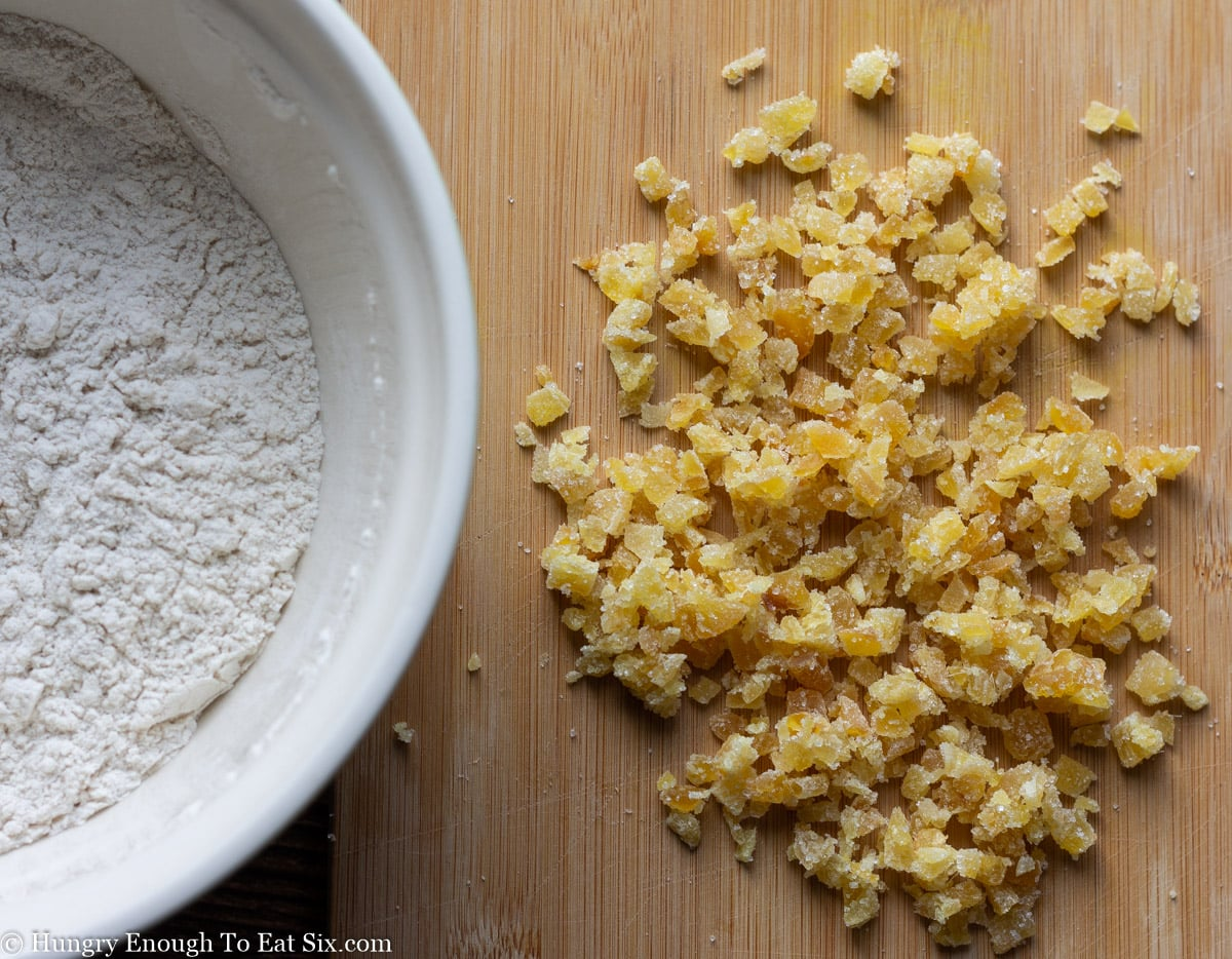 Pile of minced candied ginger next to a bowl of flour