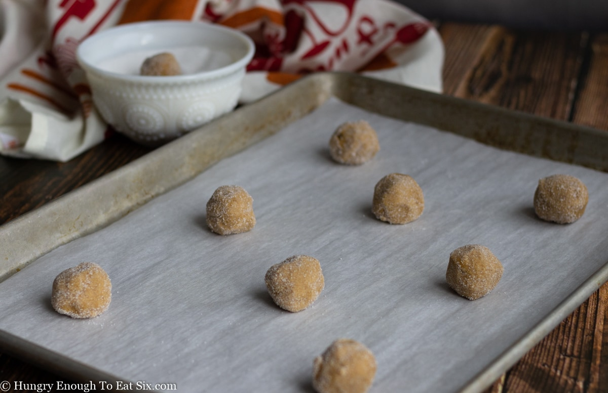 Balls of cookie dough on a lined baking sheet