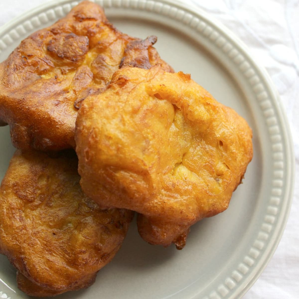 Three pumpkin fritters on a small gray plate