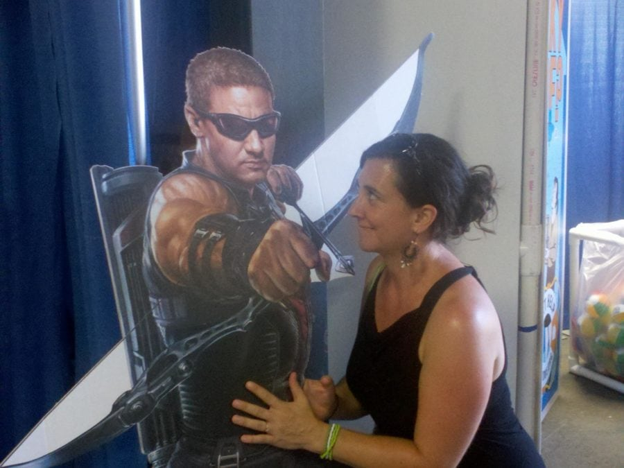 Nancy Mock with a cardboard standee of Hawkeye from the Avengers movie.