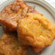 Orange pumpkin fritters on a gray plate