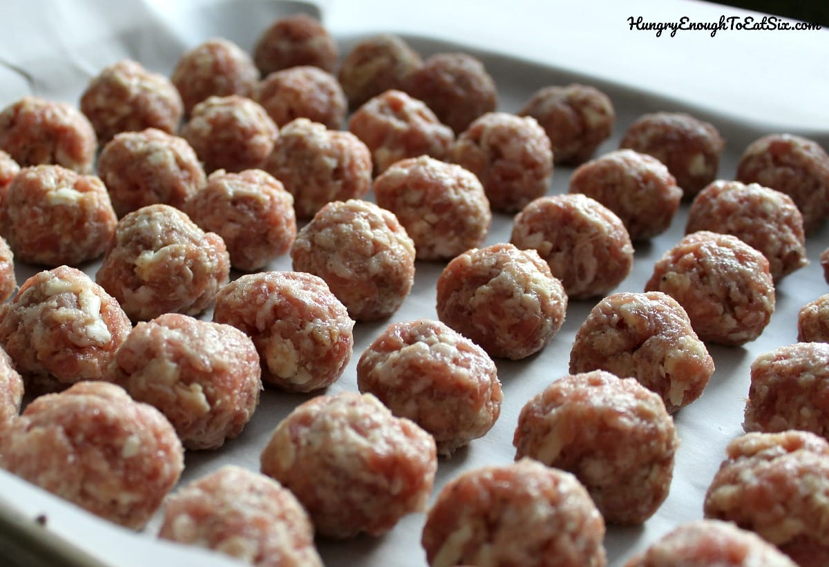Rows of raw meatballs on a baking sheet
