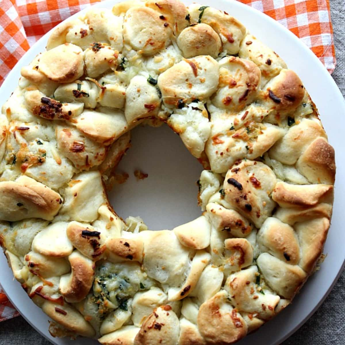 Baked circle of pull apart style bread on a white and red plate