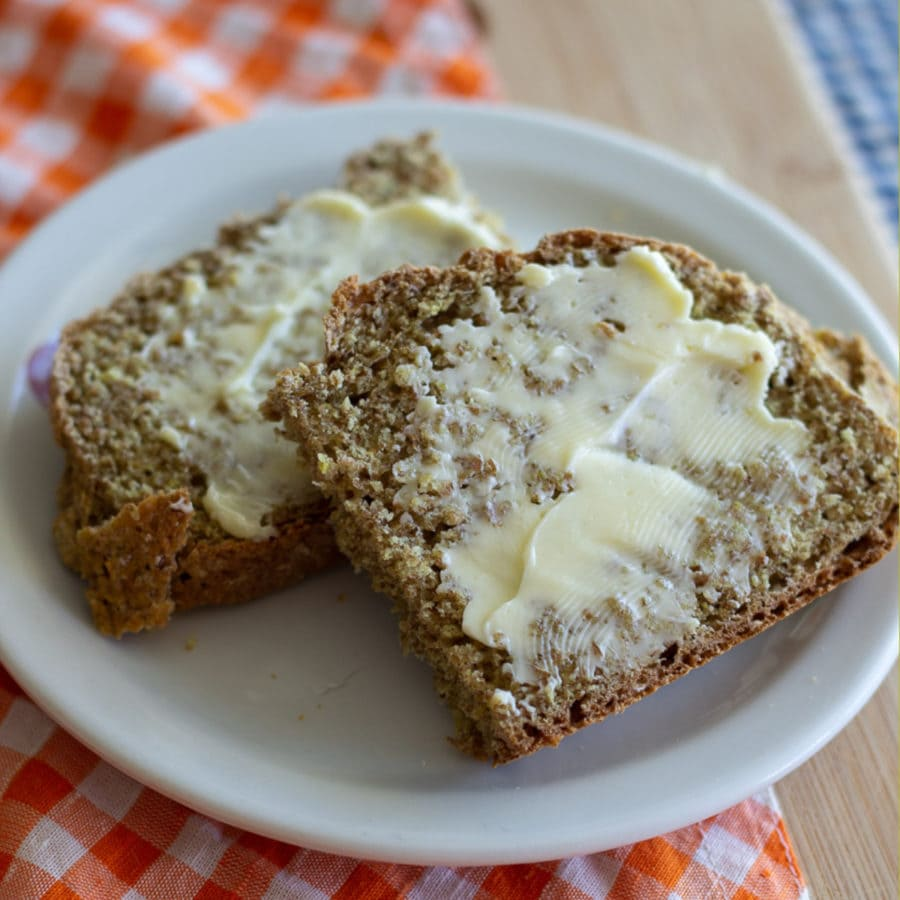 Irish brown bread buttered and on a white plate.