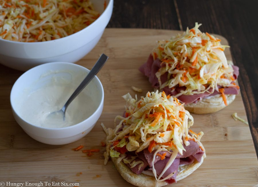 Partially assembled corned beef and cabbage slaw sandwiches.