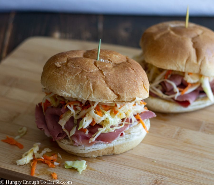 A cutting board with corned beef and cabbage slaw sandwiches