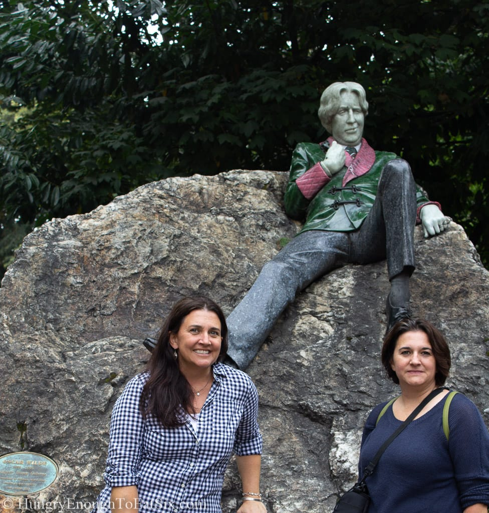 Two women by a large rock and statue
