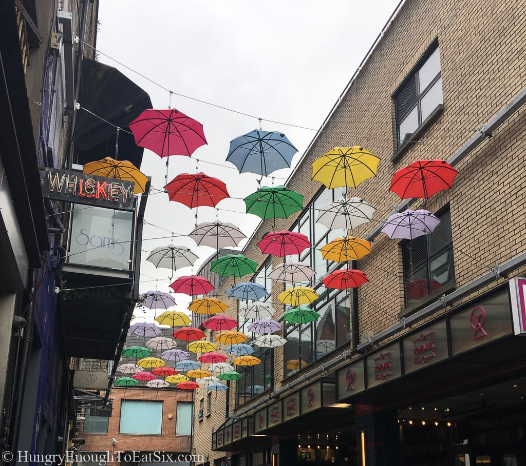 Colorful umbrellas opened above an alley