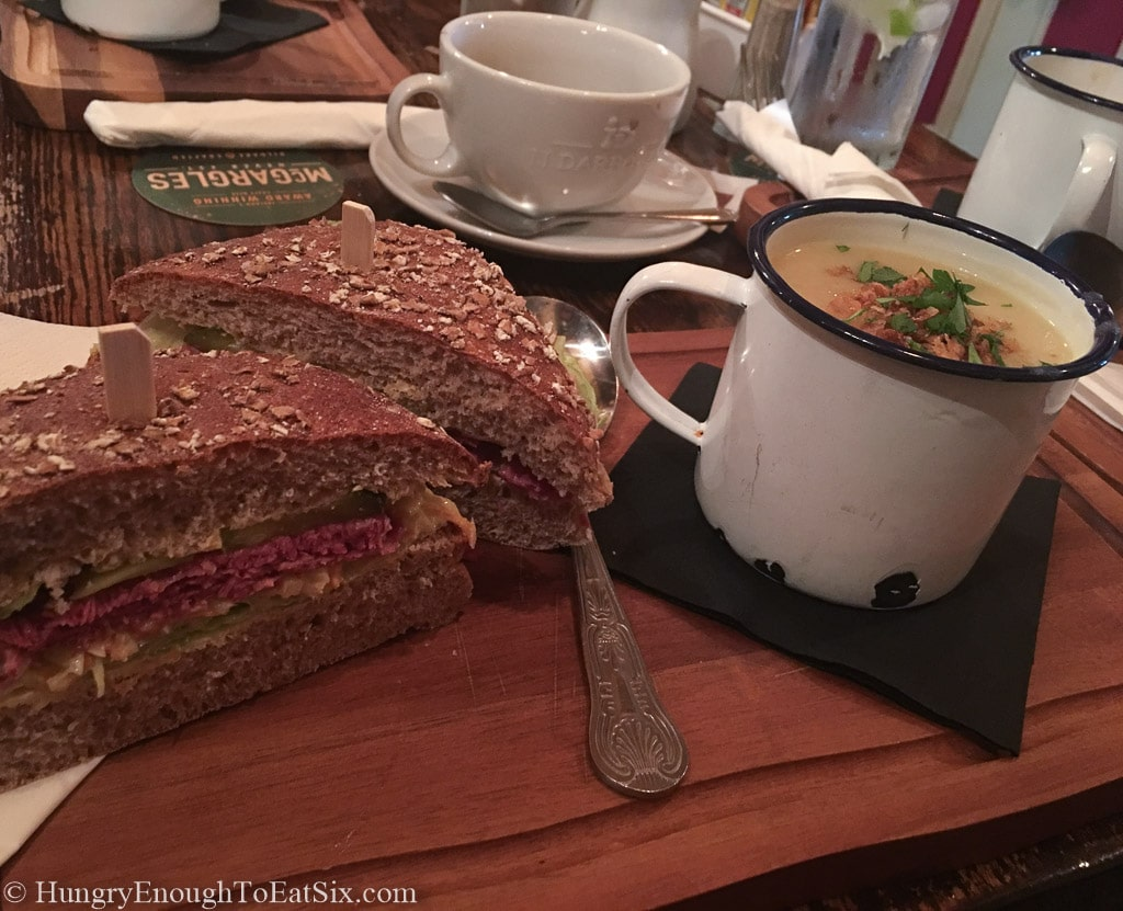 Wheat bread sandwich next to a cup of soup.