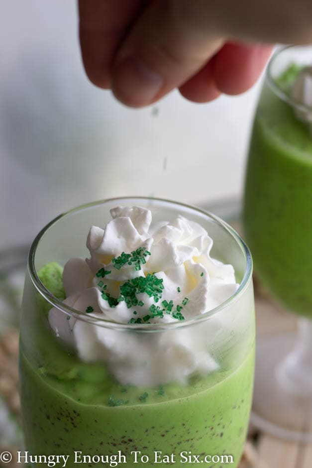 Green sprinkles and cream on a green milkshake
