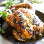 Roast chicken in a cast iron pan with parsley leaves