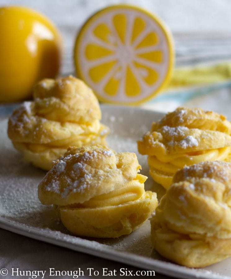Vertical image of filled cream puffs on a white plate dusted with confectioner's sugar