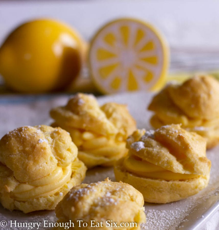 Image of filled cream puffs on a white plate dusted with confectioner's sugar