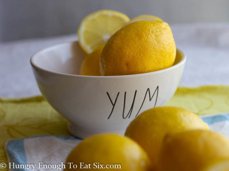 Lemons and lemon slices in a white bowl that says Yum.