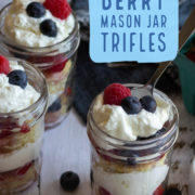 Glass jars holding layers of fruit and cream with berries scattered around.