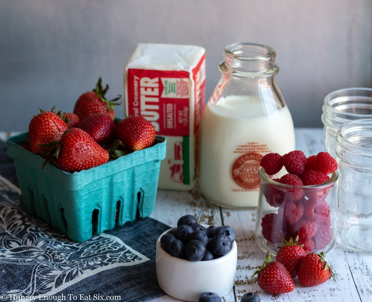 Ingredients to make fruit trifles including butter, cream, and berries.
