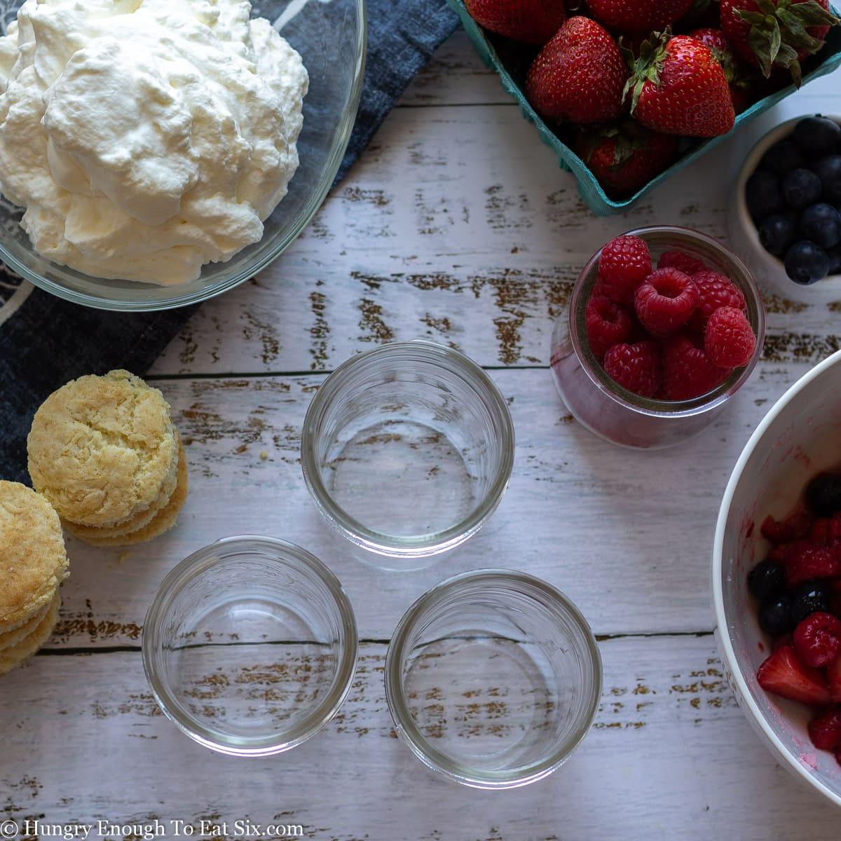 Ingredients for trifles including raspberries, whipped cream. shortcake and jars.