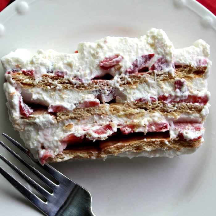 Fork and white plate holding a slice of strawberries and cream icebox cake.