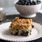 Blueberry coffee cake slice on a white plate.