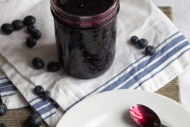 Blueberry sauce in a jar and on a spoon lying on a plate.