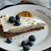 Creamy icebox pie on white plate with cookies and blueberries around it.