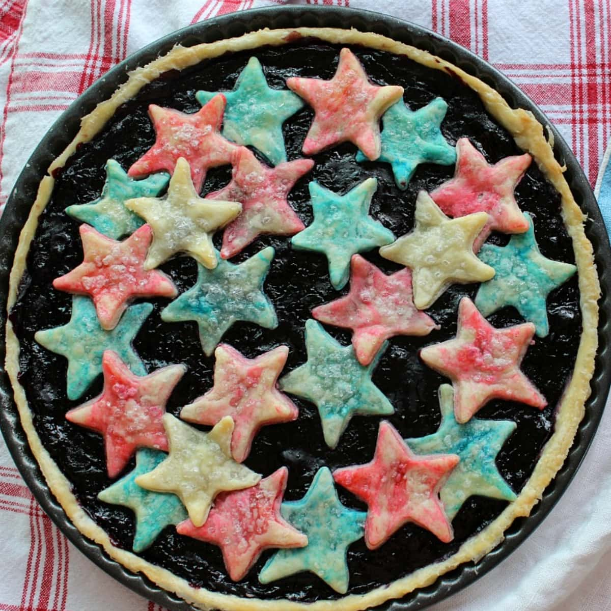 Fruit tart with red and blue stars sitting on a gingham cloth.