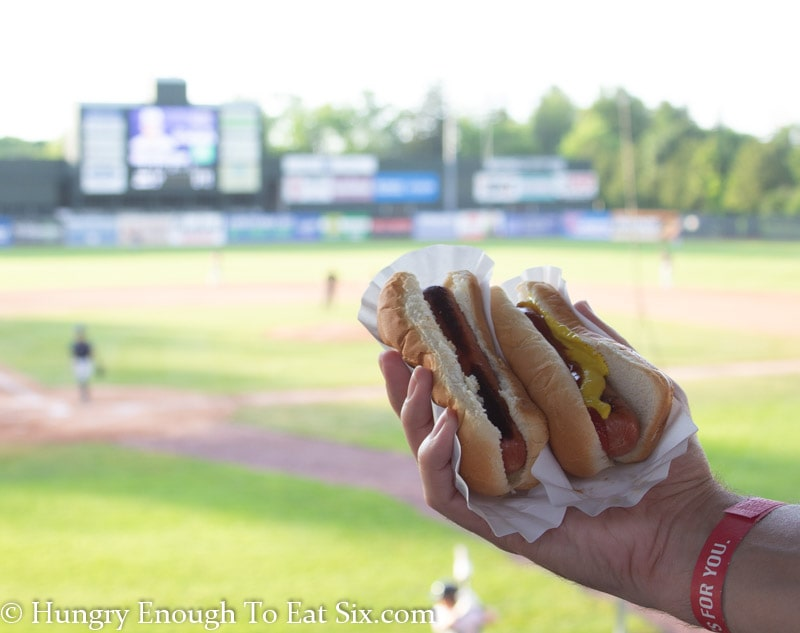 A hand holding two hot dogs in buns with the Lake Monsters VT baseball field in background.