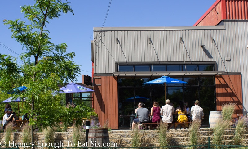 Patio outside of Switchback Brewery taproom, orange and grey siding and dark glass windows.