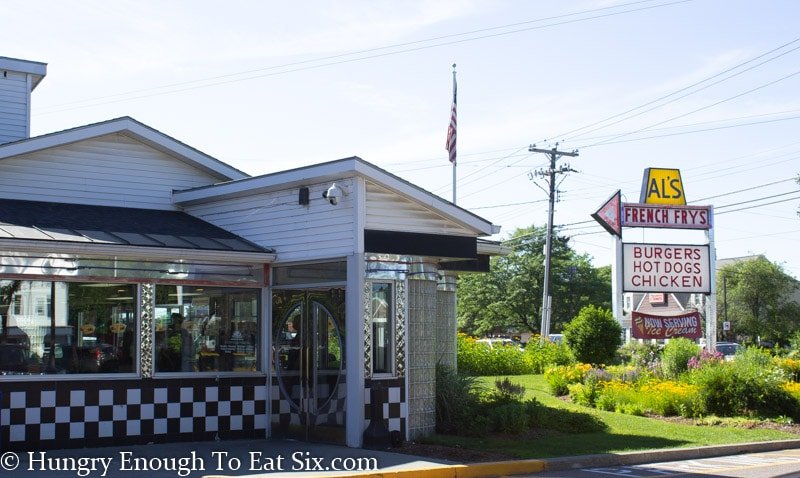 Al's French fries entrance with chrome trim and black and white tile, tall vintage side in background by road.