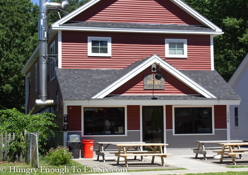 Front of Bessery's Butcher shoppe, red siding with grey and white trim and picnic tables out front.