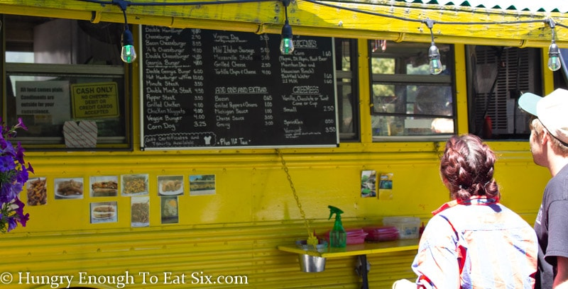 Menu on the side of a yellow bus operating as a snack bar, 2 people looking at menu.