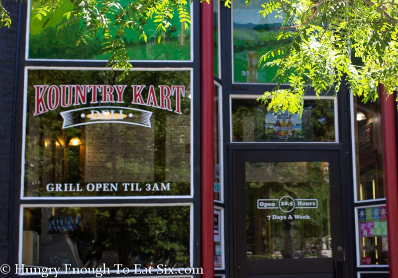 Outside of Kountry Kart Deli, large windows with lettering and black, red & white trim.