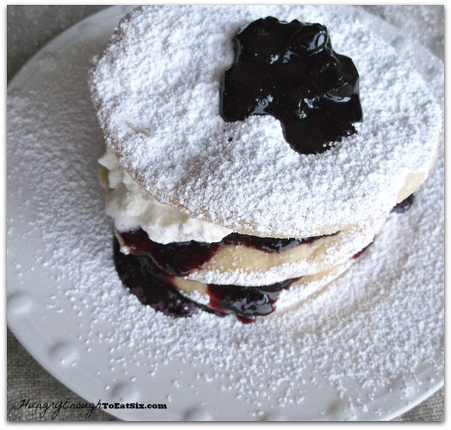 Sugar dusted stack of fruit, pastry and cream