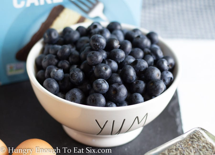 Bowl of fresh blueberries. Bowl says YUM.