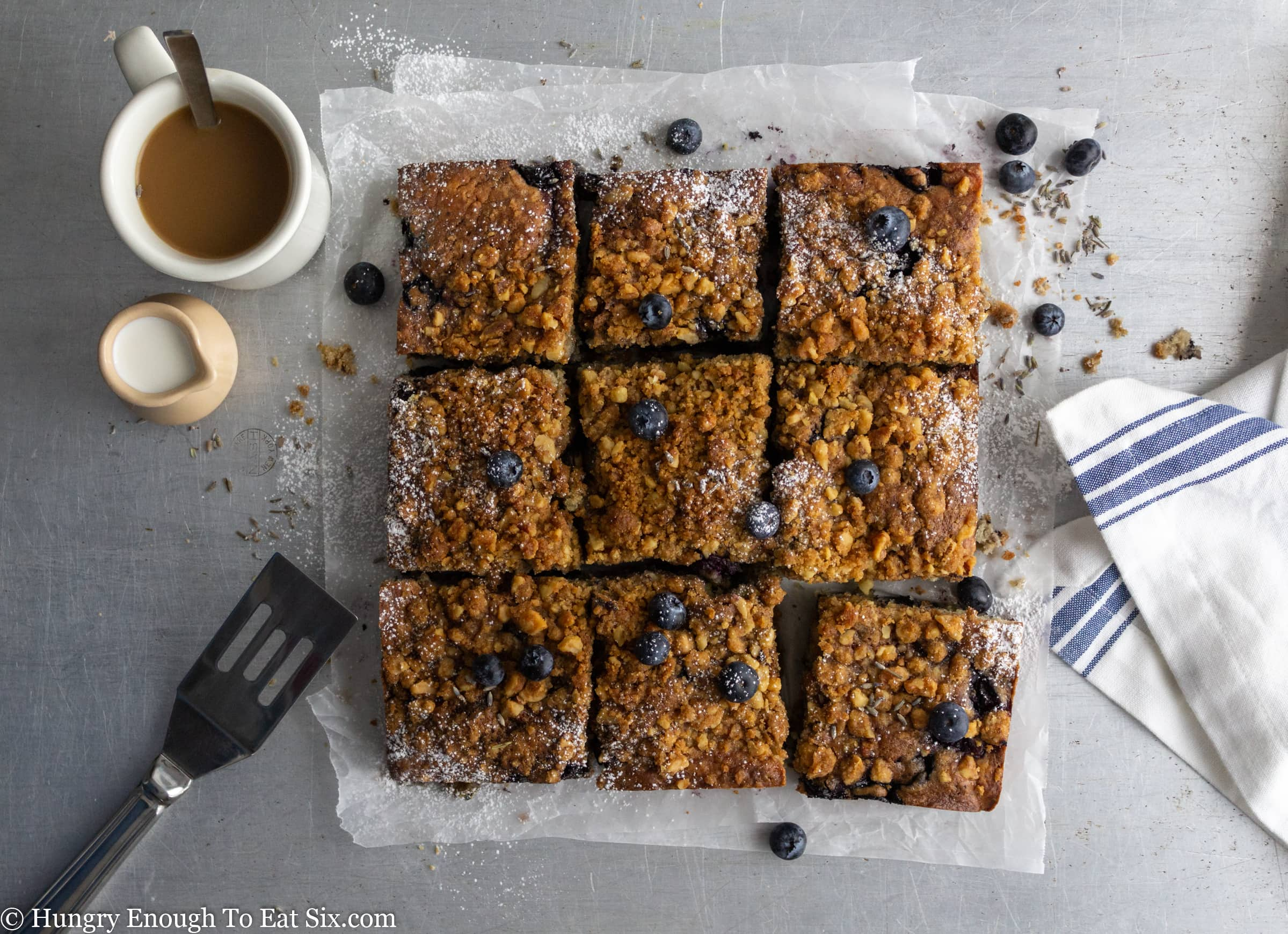 Nine squares of crumble topped coffee cake with blueberries.