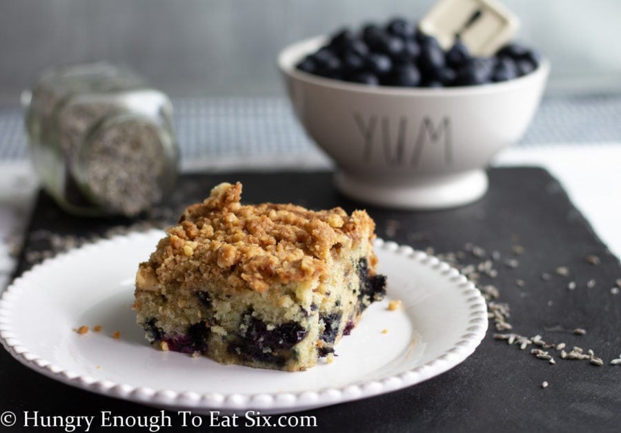 Slice of blueberry coffee cake on a white plate and black slate board, bowl of blueberries in background.