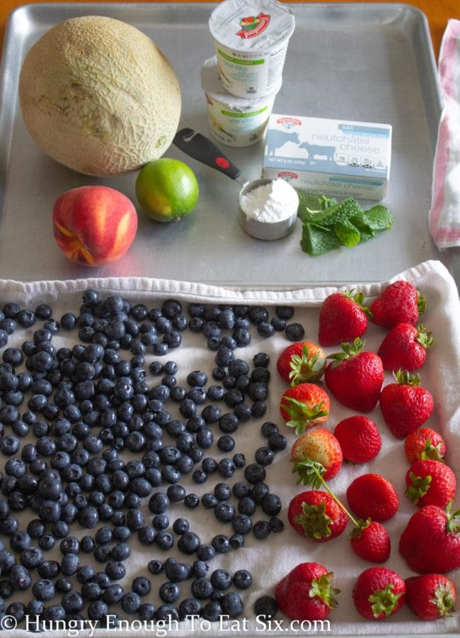 Blueberries and strawberries on a cloth with a peach, lime, cream cheese, cantaloupe and yogurt behind them.
