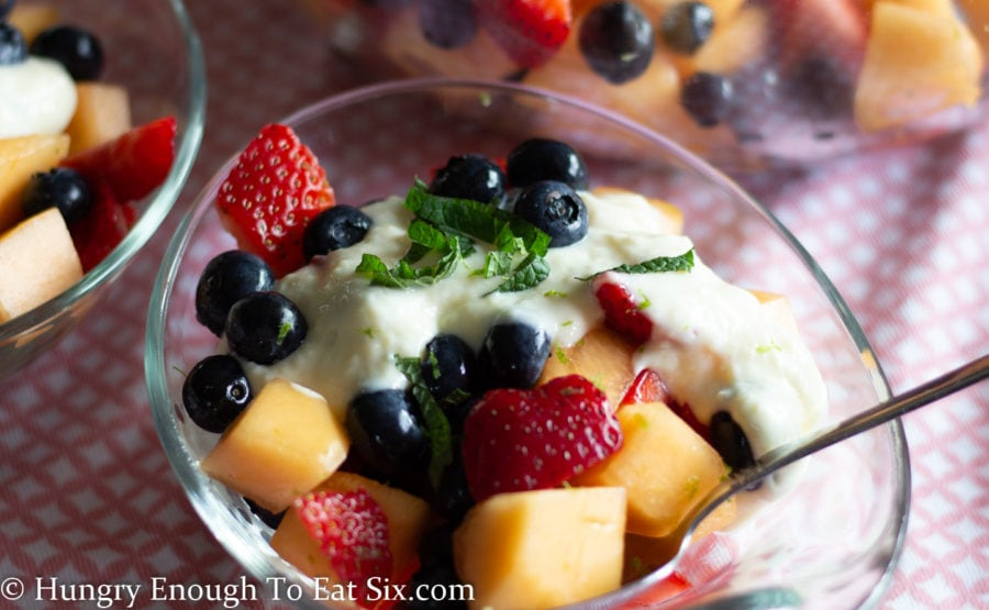 Fruit salad in a clear bowl topped with sweet cream sauce and mint leaves.