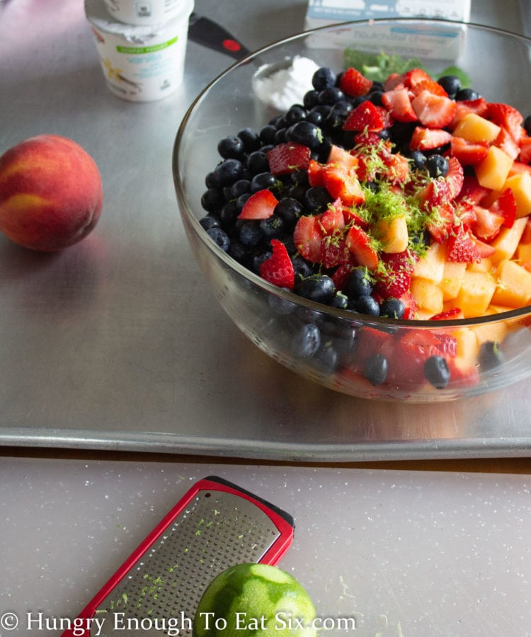 Blueberries, strawberries and cantaloupe in a clear bowl topped with lime zest, a zester and lime in foreground.