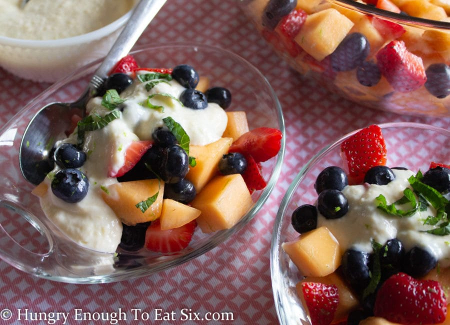 Clear bowls of blueberry strawberry and cantaloupe fruit salad with a creamy sweet sauce and mint.