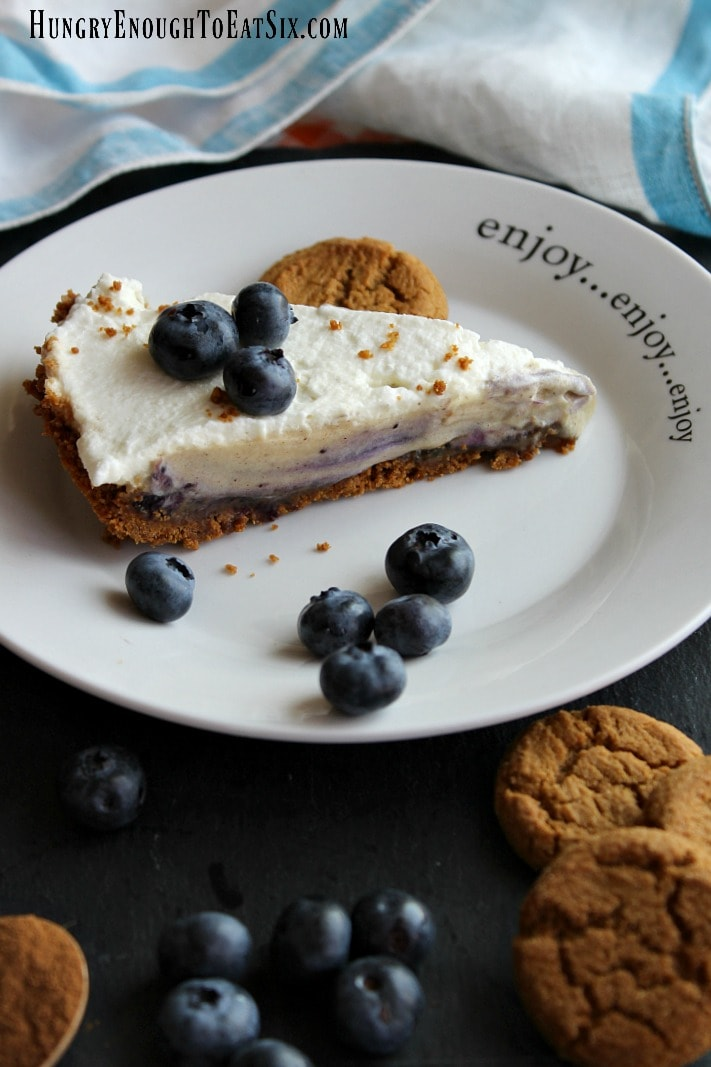 Cookies and berries on a plate with a slice of cream pie