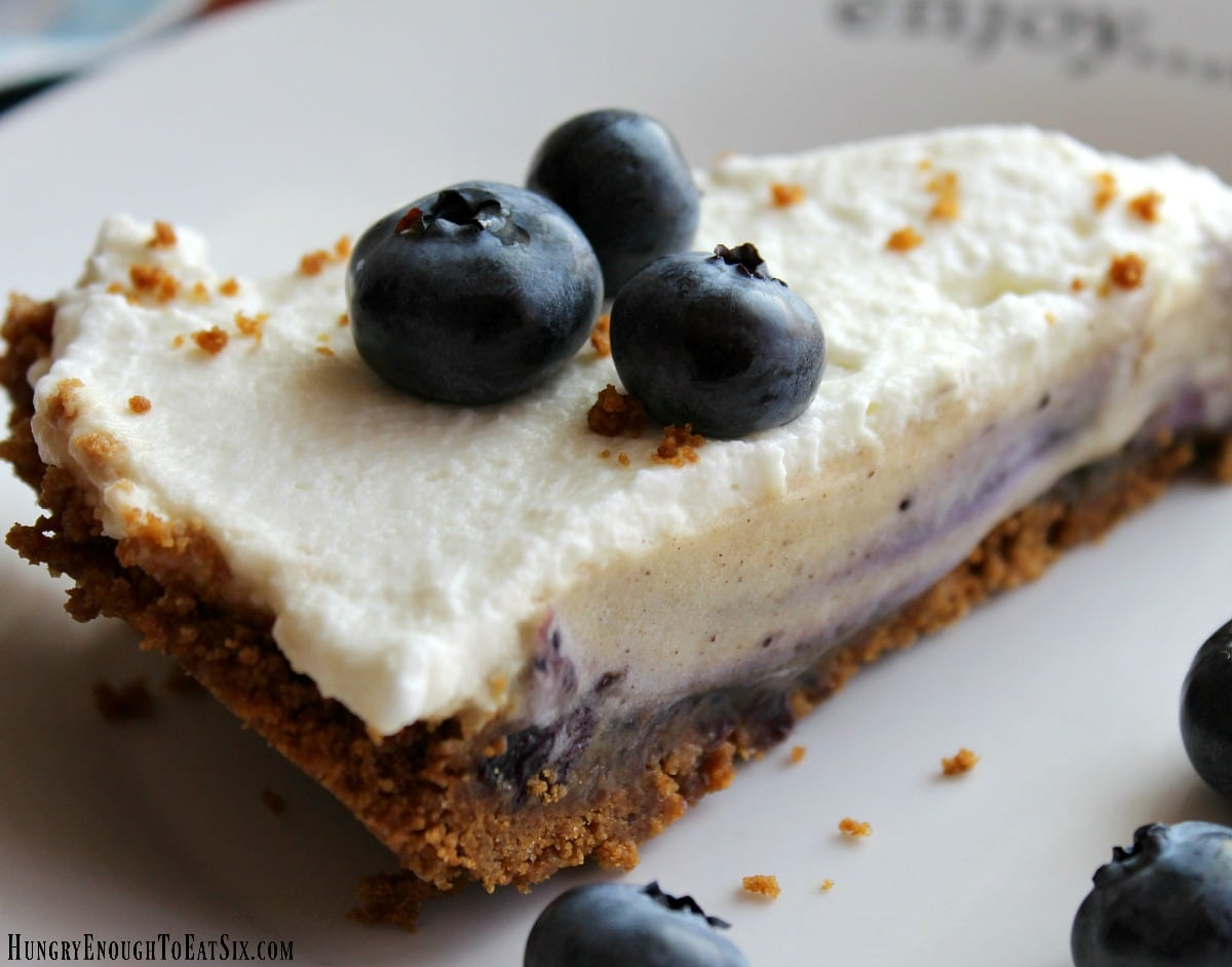 Blueberry and cream pie on a plat with whole berries