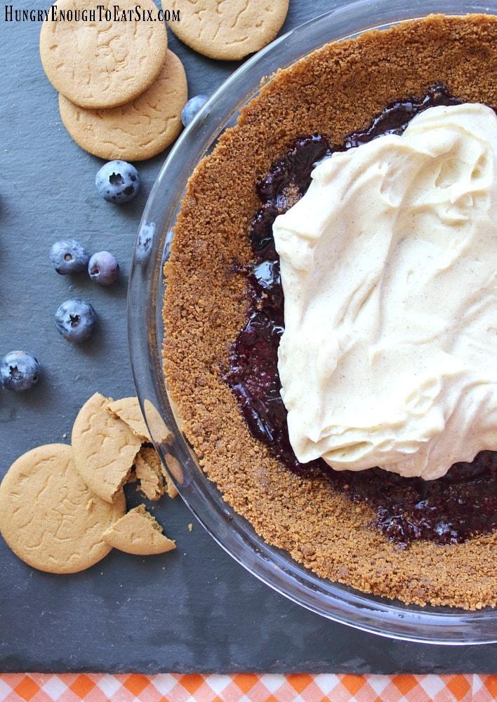 Graham cracker pie crust holding blueberry sauce and cream