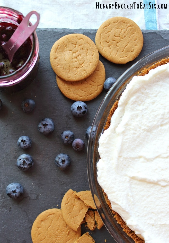 Cookies and berries near a cream filled pie crust