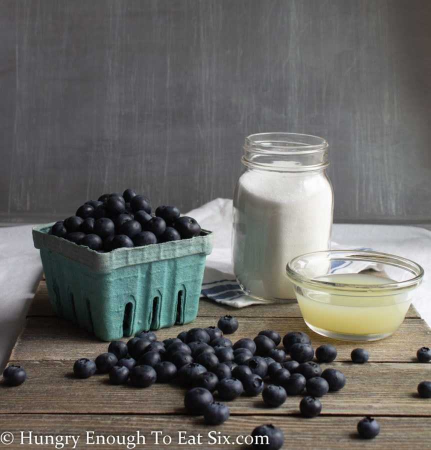Blueberries in a green container, white sugar and lemon juice on a wood surface.