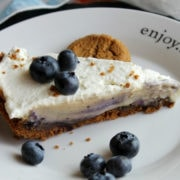 Slice of icebox pie on a white plate, white filling in pie and blueberries around.