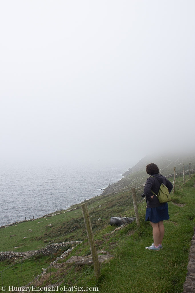 Woman standing on a slope looking at ocean